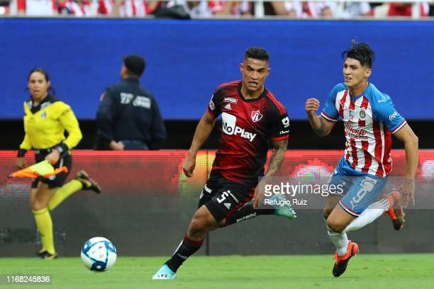 Alan Pulido of Chivas fights for the ball with Anderson Santamaría of Atlas during the 9th round match between Chivas and Atlas as part of the Torneo...