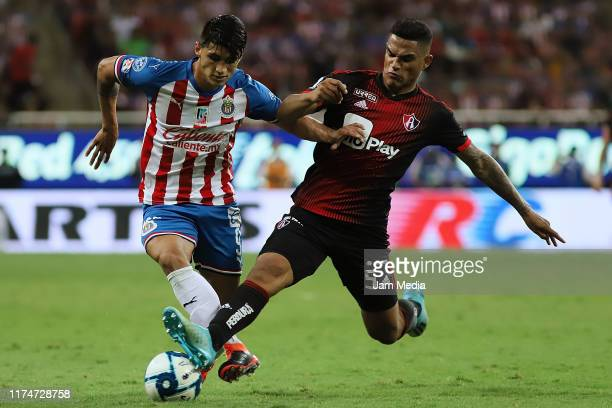 Alan Pulido of Chivas fights for the ball with Anderson Santamaria of Atlas during the 9th round match between Chivas and Atlas as part of the Torneo...