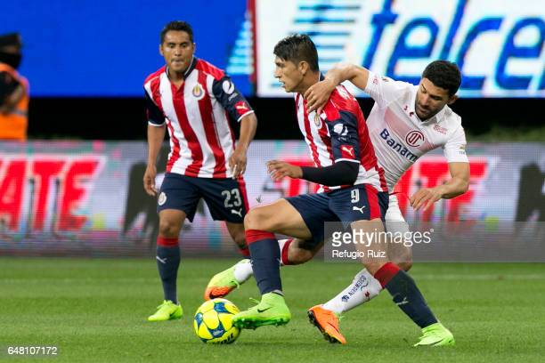 Alan Pulido of Chivas fights for the ball with Antonio Naelson of Toluca during the 9th round match between Chivas and Toluca as part of the Torneo...