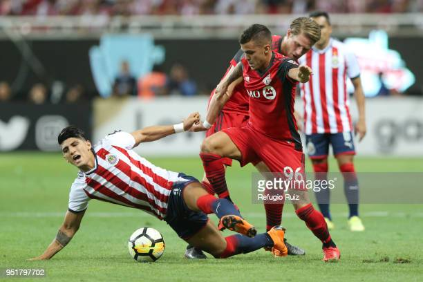 Alan Pulido of Chivas fights for the ball with Auro Junior of Toronto FC during the second leg match of the final between Chivas and Toronto FC as...