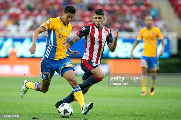 Alan Pulido of Chivas fights for the ball with Hugo Ayala of Tigres during the 10th round match between Chivas and Tigres as part of the Torneo...