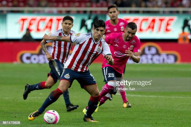 Alan Pulido of Chivas fights for the ball with Mario Osuna of Morelia during the 13th round match between Chivas and Morelia as part of the Torneo...