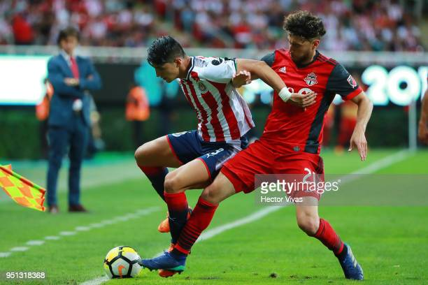 Alan Pulido of Chivas struggles for the ball with Jonathan Osorio of Toronto FC during the second leg match of the final between Chivas and Toronto...