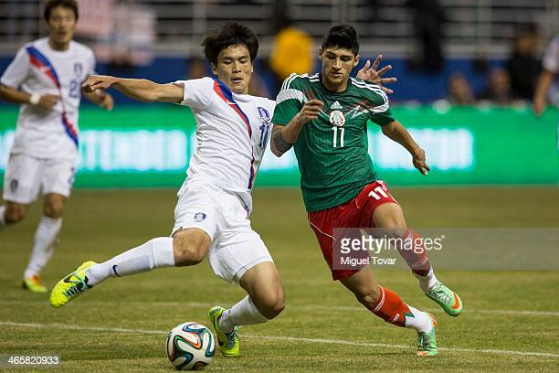 Alan Pulido of Mexico fights for the ball with Lee KeunHo of Korea during a FIFA friendly match between Mexico and South Korea at Alamodome Stadium...