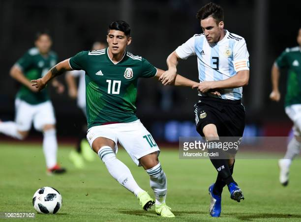 Alan Pulido of Mexico fights for the ball with Nicolas Tagliafico of Argentina during a friendly match between Argentina and Mexico at Mario Kempes...