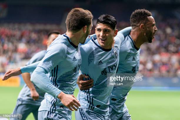 Alan Pulido of Sporting Kansas City celebrates with teammates Ilie Sanchez and Khiry Shelton after scoring a goal on the Vancouver Whitecaps during...