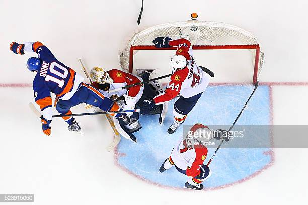 Alan Quine of the New York Islanders collides with Roberto Luongo of the Florida Panthers in Game Six of the Eastern Conference First Round during...