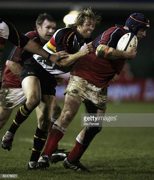 Alan Quinlan of Munster charges through the challenge of Percy Montgomery during the Celtic league match between Newport Gwent Dragons and Munster at...