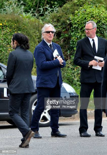 Alan Rickman stands with other mounrners as he leaves St George's church in Dittisham Devon following the funeral of Rik Mayall