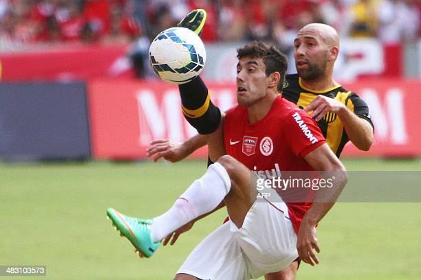 Alan Ruschel player of Brazilian Internacional and Baltazar Silva player of Uruguayan Penarol vie during a friendly match held to inaugurate the...