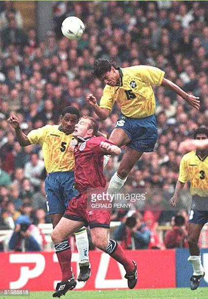 Alan Shearer of England goes up for the ball with Cesar Sampaio and Marcio Santos of Brazil 11 June during the final of the UMBRO Cup between England...
