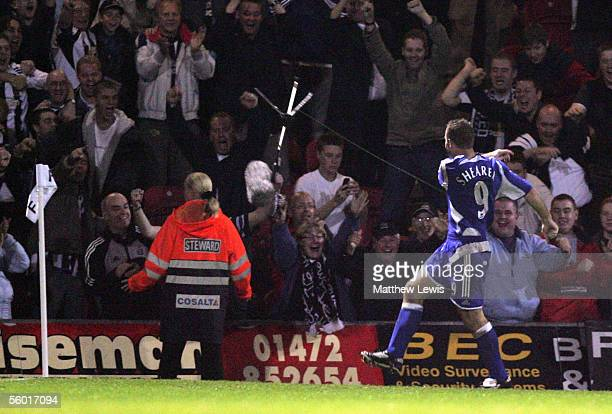 Alan Shearer of Newcastle United celebrates his goal by kicking a TV microphone stand during the Carling Cup Third round match between Grimsby Town...