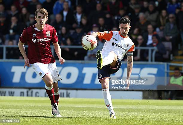 Alan Sheehan of Luton Town plays the ball watched by John Marquis of Northampton Town during the Sky Bet League Two match between Northampton Town...