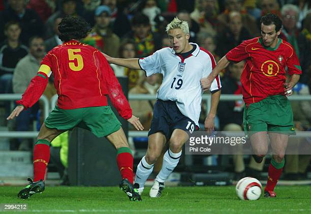 Alan Smith of England battles with Fernando Couto and Petit of Portugal during the International Friendly match between Portugal and England at the...