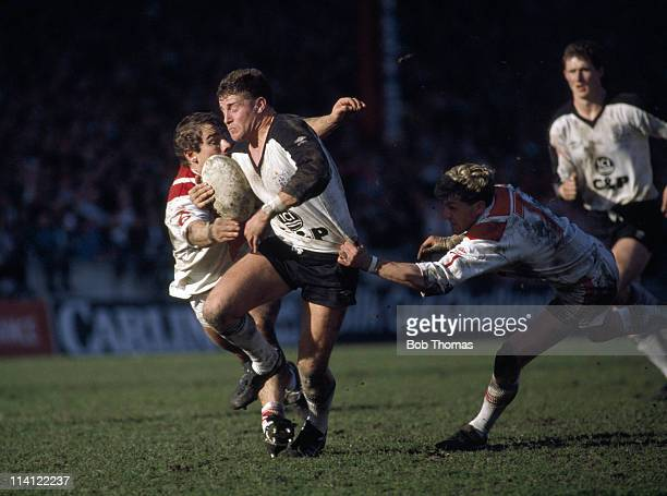 Alan Tait of Widnes is tackled by Darren Bloor and Neil Holding of St Helens during the Silk Cut Challenge Cup Rugby League Semi-final at Wigan on...