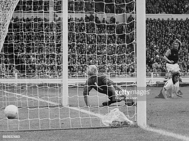Alan Taylor of West Ham United shoots the ball between the legs and into the net of Fulham goalkeeper Peter Mellor to score as Fulham defender John...