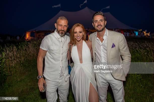 Alan Vladusic Alisa Jacobs and Marc Sampogna attend Hamptons Magazine Chic at the Beach with John Legend on July 13 2019 in Montauk New York