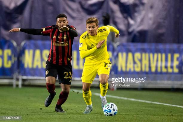 Alan Winn of the Nashville SC moves with the ball against Jake Mulraney of the Atlanta United during the second half at Nissan Stadium on February 29...