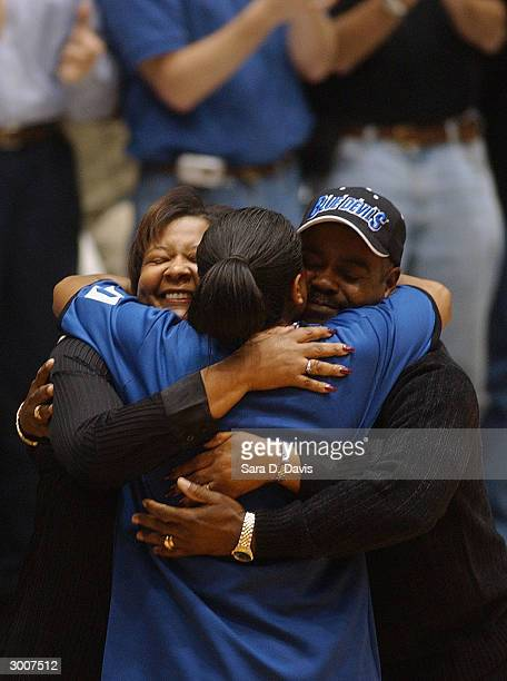 Alana Beard of the Duke Blue Devils is hugged by her mother Marie and father LeRoy as she has her number 20 retired in a ceremony prior to the game...