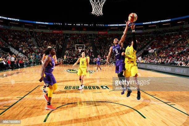 Alana Beard of the Los Angeles Sparks and Alysha Clark of the Seattle Storm reach for the ball on June 28 2018 at Key Arena in Seattle Washington...