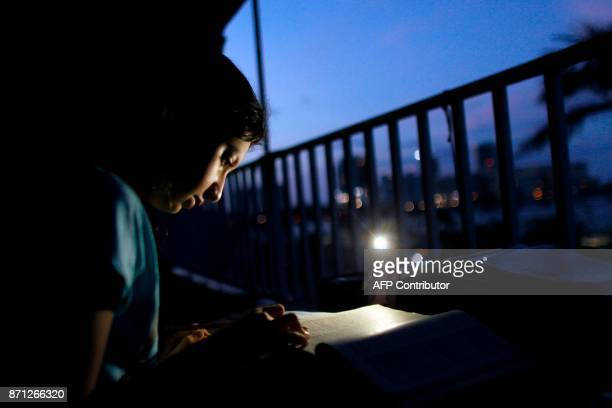 Alana Rivera age 10 does her daily homework in her apartment balcony lit by a cell phone light in San Juan Puerto Rico November 6 2017 The school...