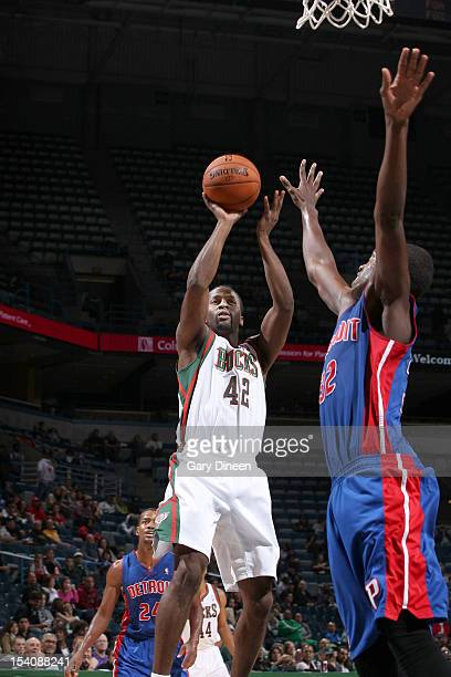 Alando Tucker of the Milwaukee Bucks shoots against Khris Middleton of the Detroit Pistons during the NBA preseason game on October 13 2012 at the...