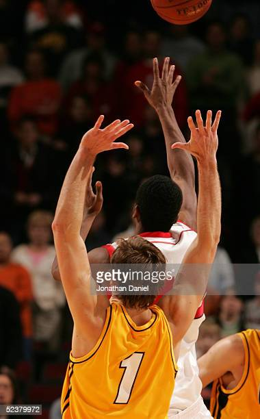 Alando Tucker of the Wisconsin Badgers attempts and makes a 3point gamewinning shot at the buzzer t bet the Iowa Hawkeyes 5956 past Adam Haluska of...
