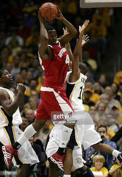 Alando Tucker of the Wisconsin Badgers looks to pass the ball in the air against David Cubillan of the Marquette Golden Eagles December 9 2006 at the...