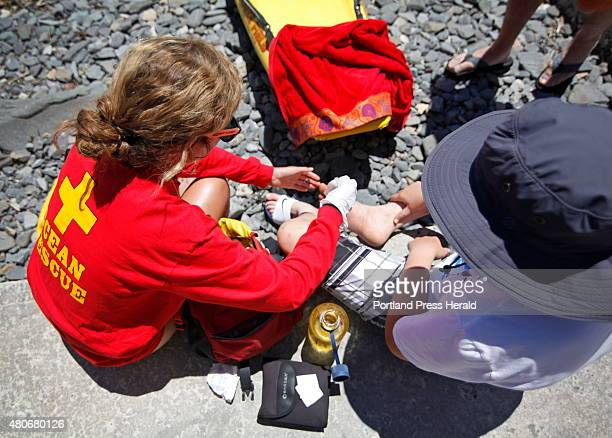 Alanna Eaton bandages a foot injury for a boy who slipped on some rocks Tuesday June 30 2015 at York Harbor Beach Eaton says she has had to do more...