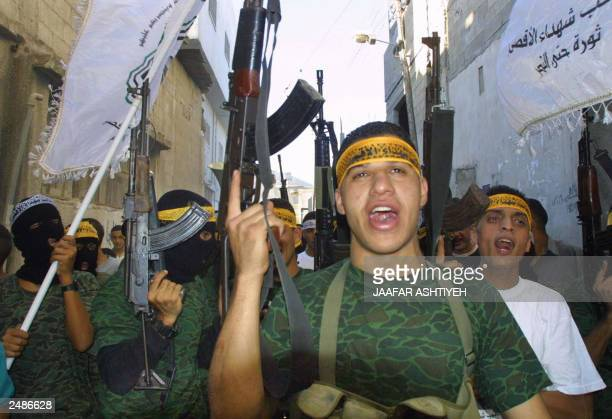 Al-Aqsa Martyrs Brigade militants shout while they hold their weapons during a demonstration in support of Palestinian leader Yasser Arafat in the...