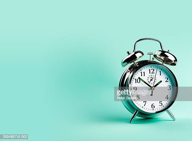 Alarm clock, against green background, close-up