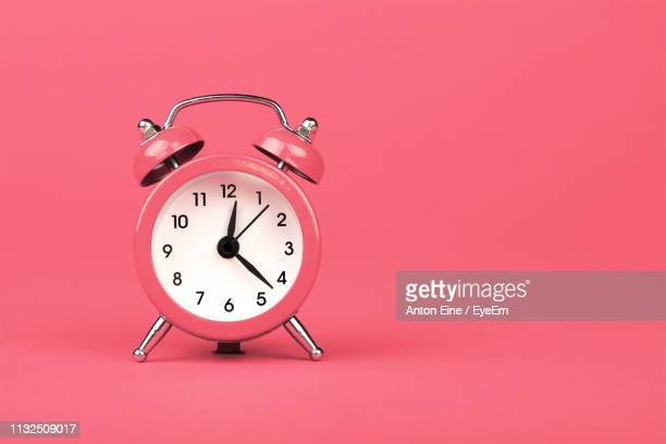 alarm clock against pink background - klok stockfoto's en -beelden