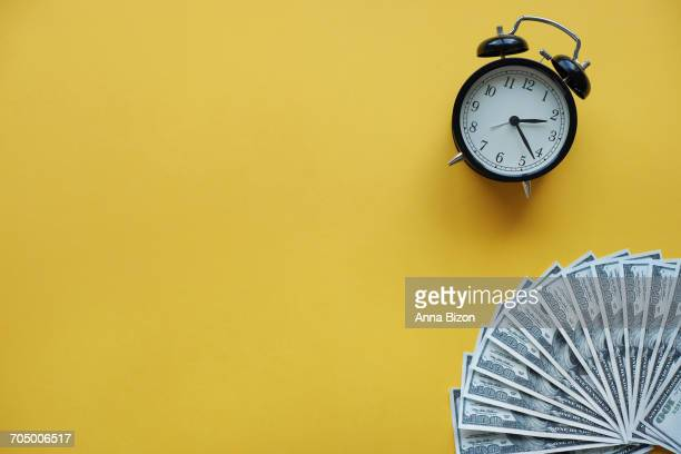 Alarm clock and American one hundred dollar bills. Debica, Poland