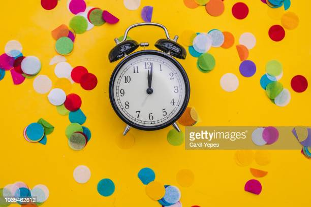 alarm clock and confetti in yellow background