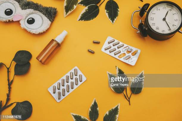 alarm clock and sleeping pills in yellow background.Insomnia concept