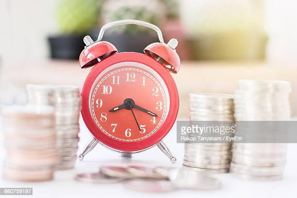 Alarm Clock And Stacked Coins On Table