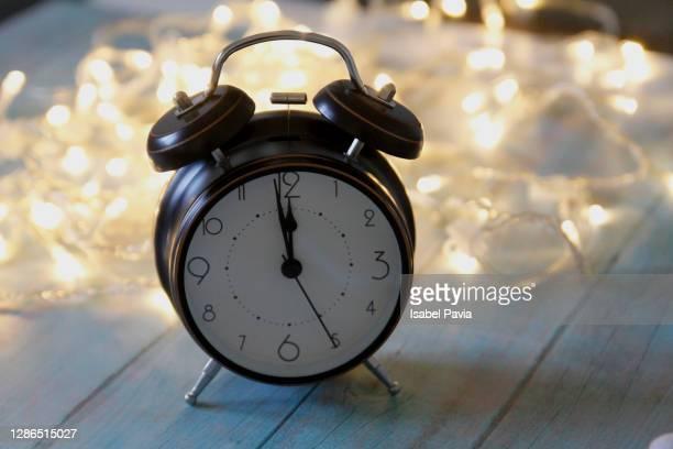 alarm clock at 12 o'clock, with christmas lights - 新年レセプション ストックフォトと画像