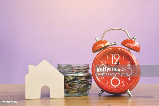 Alarm Clock By Coins In Container With Model House On Wooden Table Against Wall