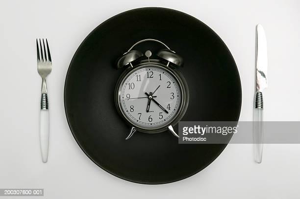 Alarm clock lying on black plate