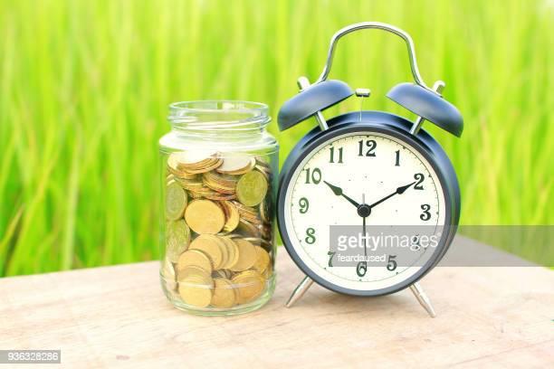 Alarm clock on a table next to a jar