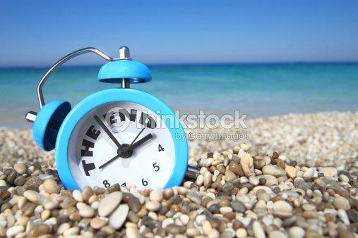Alarm Clock On Beach Signaling End Of Summer Stock Photo