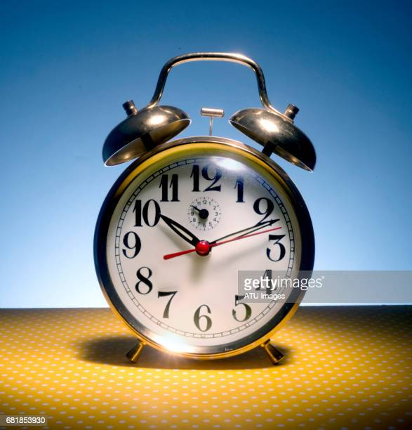 alarm clock on bright colored background