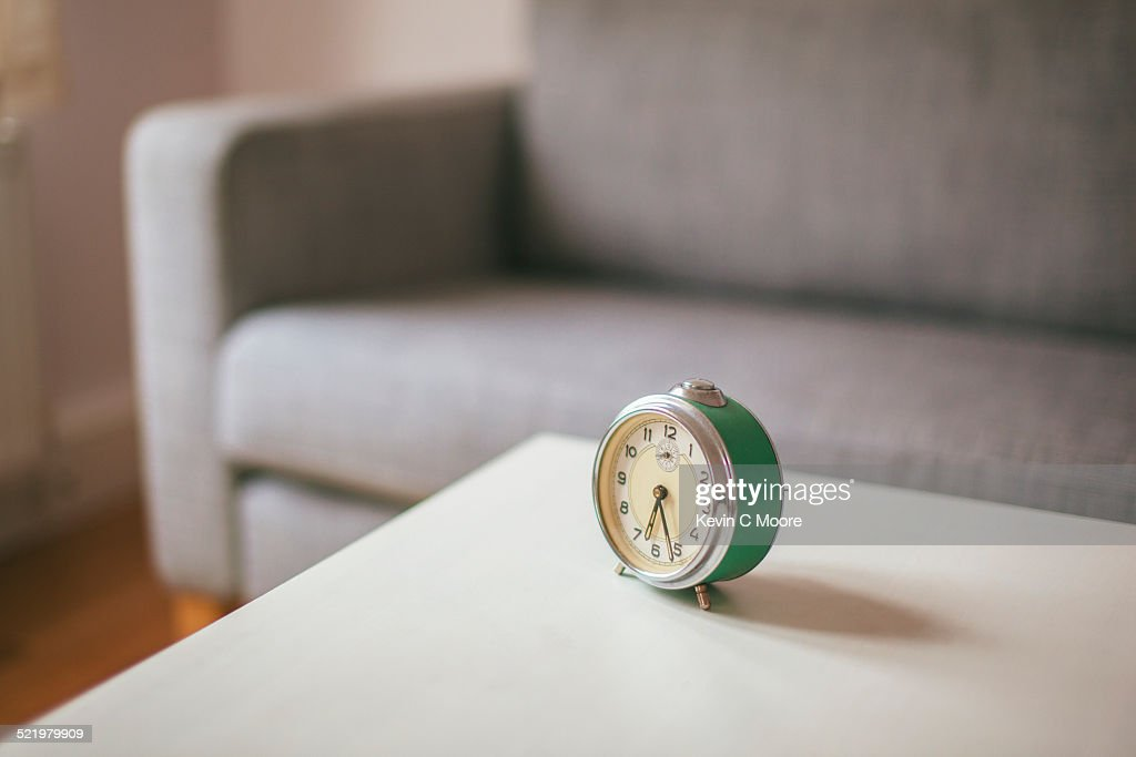 Alarm clock on coffee table in living room : Stock Photo