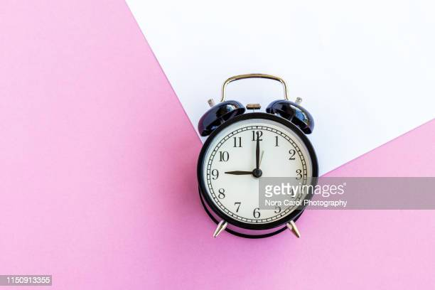 alarm clock on multi colored background - daylight saving time stock pictures, royalty-free photos & images