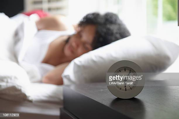 Alarm clock on night stand, Black woman sleeping in background