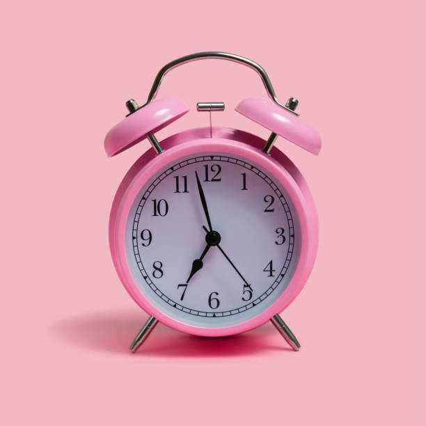 Alarm clock on pink background