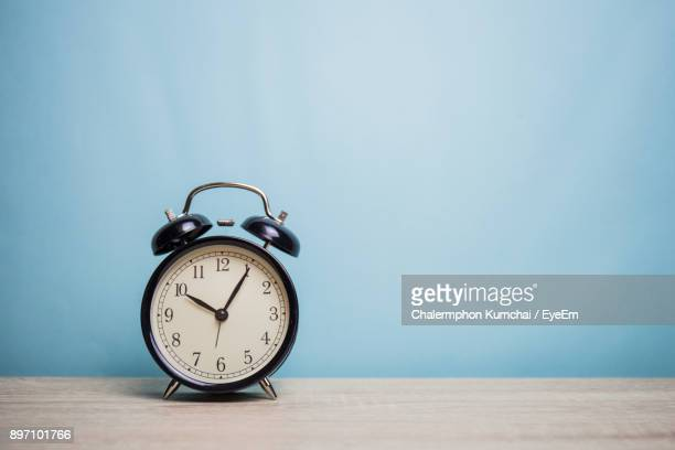 Alarm Clock On Table Against Wall