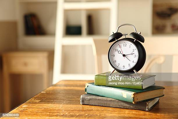 Alarm Clock On Top Of Books At Table