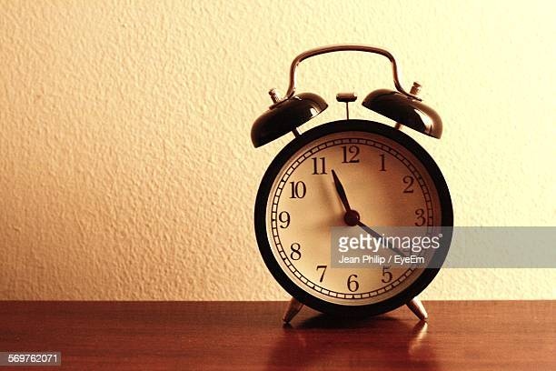 Alarm Clock On Wooden Table At Home