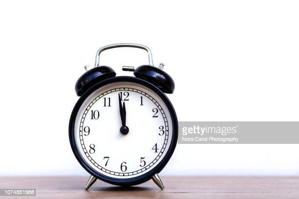 alarm clock pointing at 12 midnight - midnight stock pictures, royalty-free photos & images